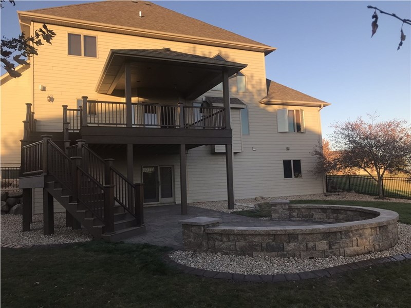 2 story home with a deck and patio area