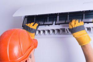 man replacing air conditioner filter