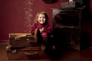 dirty child sitting in a suitcase