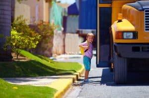 kid getting on a school bus
