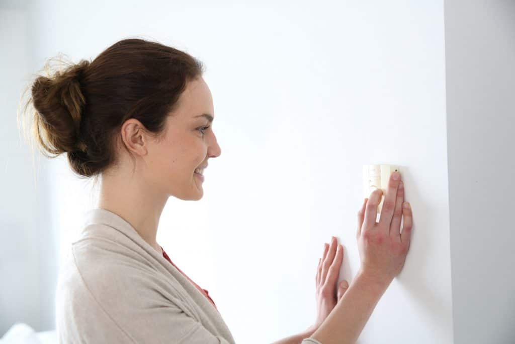 Woman adjusting thermostat heater as temperatures cool.