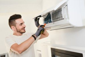 smiling man fixing air conditioner