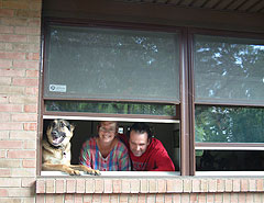 The Mobleys at home with their pet and old front window.