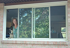 Sharon Mobley admires the new front window. Winning the grand prize allowed her the opportunity to change from double hung windows to a sliding window.
