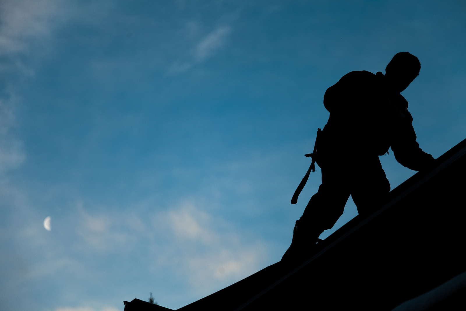Silhouette of man working on roof