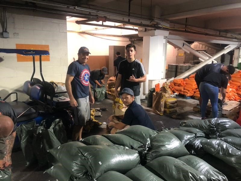 Premier Restoration Hawaii team filling sandbag in preparation for the storm